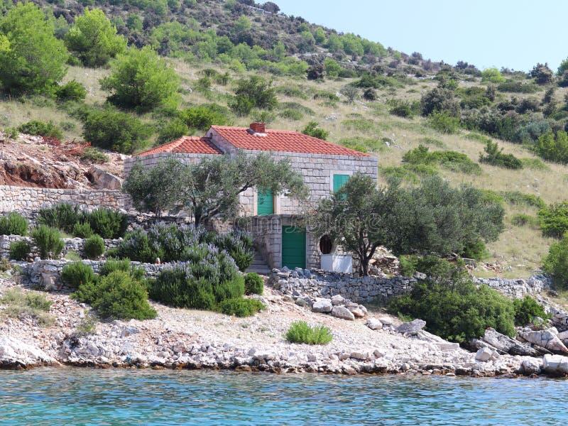 Een klein huis van de steentoevlucht op een rotsachtige berghelling op de Adriatische kust Kroatische Riviera Rust in eenzaamheid royalty-vrije stock foto