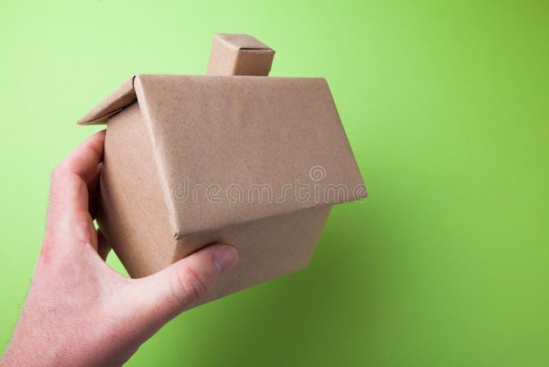 Een klein kartonhuis in zijn hand Groene Achtergrond royalty-vrije stock afbeelding