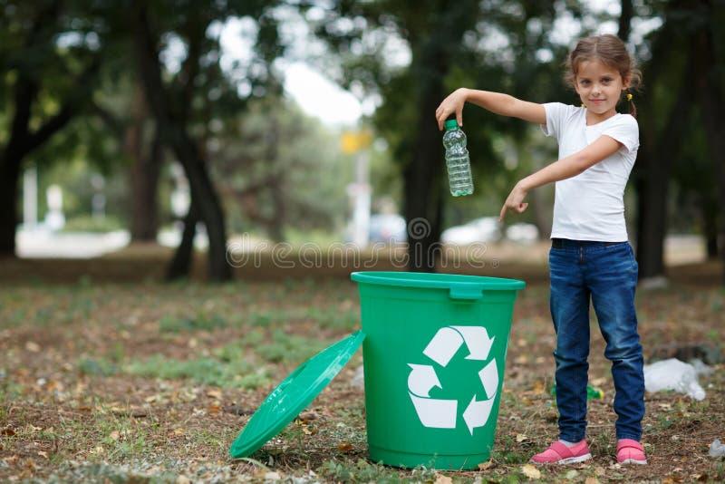 Een klein kind die het huisvuil in een groene recyclingsbak zetten op een vage natuurlijke achtergrond Het concept van de ecologi stock afbeelding