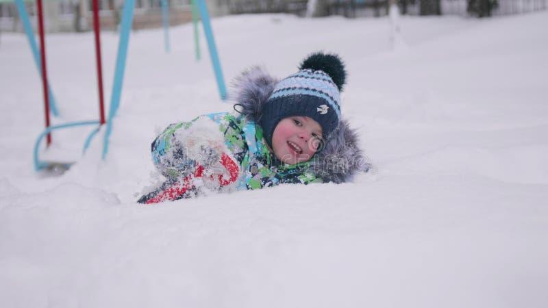 Een klein kind die met sneeuw in de winterpark spelen Liggende en glimlachende baby op witte pluizige sneeuw Pret en spelen in ve stock fotografie