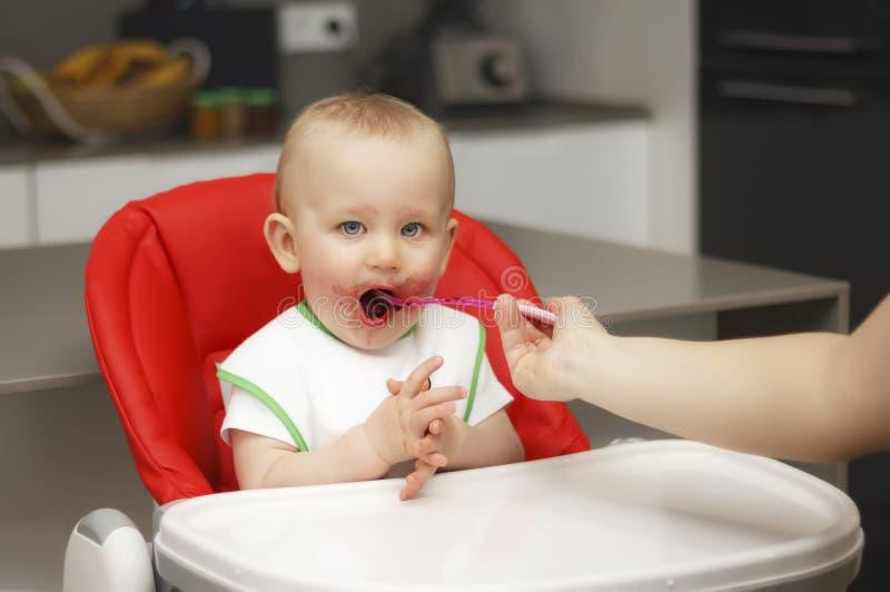 Een klein kind eet jam en het graangewas, zit op een highchair stock afbeeldingen