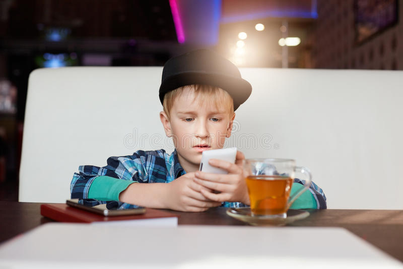 Een klein kind gekleed in modieuze kleren die in moderne binnenlandse koffie situeren, gebruikend celtelefoon, het controleren ne stock fotografie