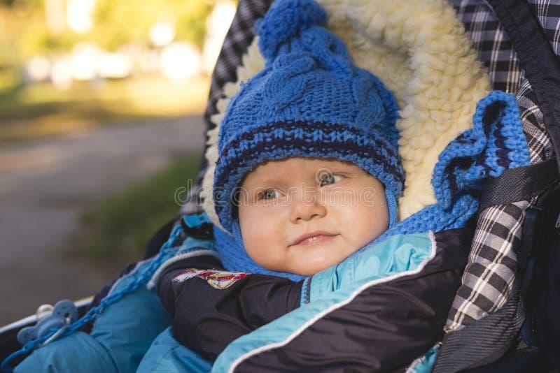 Een klein kind in een hoed en sjaalzitting in een wandelwagen stock afbeeldingen