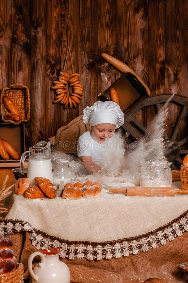 Een klein kind in een kok speelt een rol als bakker en brooddeeg stock afbeelding