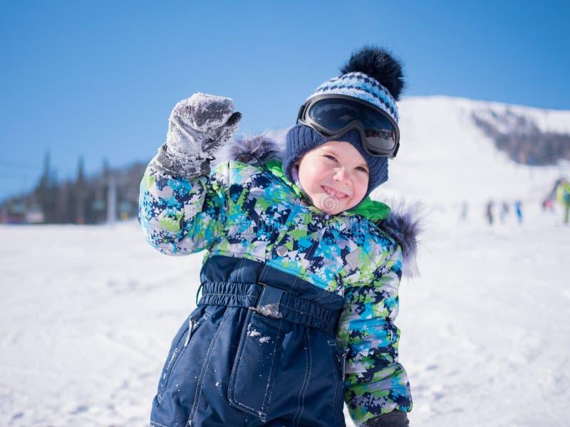 Een klein kind loopt in het de winterpark Speel en glimlachende baby op witte pluizige sneeuw Actieve rust en spelen royalty-vrije stock fotografie