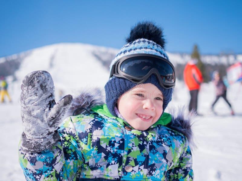 Een klein kind loopt in het de winterpark Speel en glimlachende baby op witte pluizige sneeuw Actieve rust en spelen royalty-vrije stock afbeeldingen