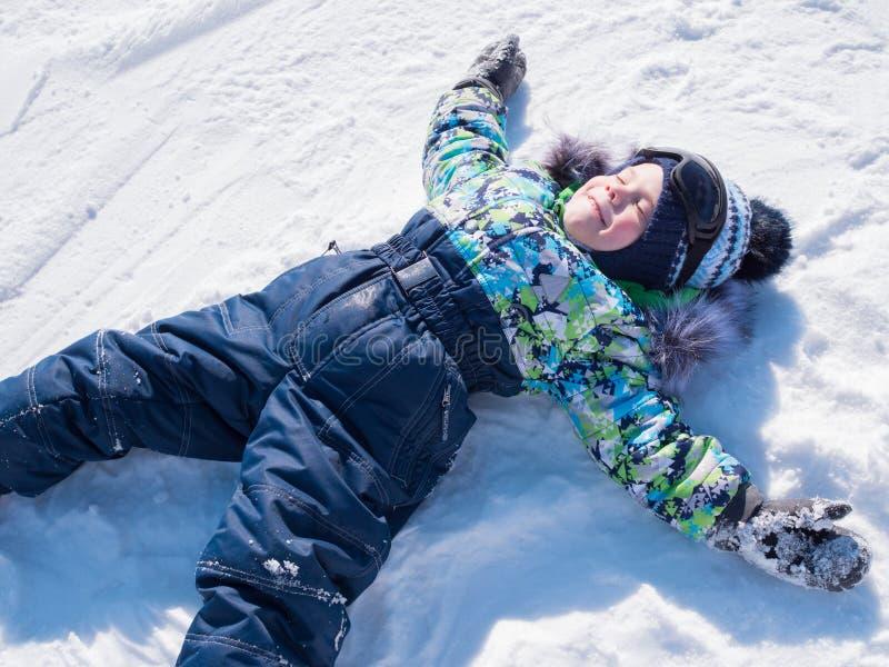 Een klein kind loopt in het de winterpark Speel en glimlachende baby op witte pluizige sneeuw Actieve rust en spelen stock foto's