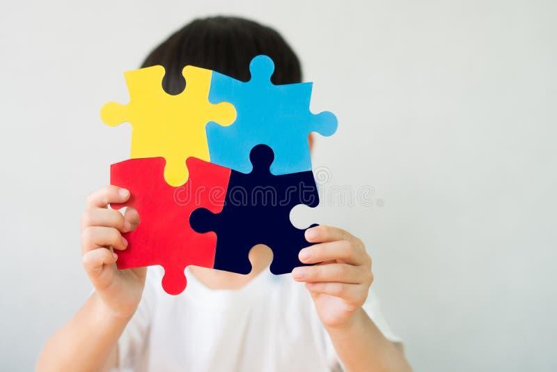 Een klein kind met een puzzelsymbool voor het bewustzijn van het publiek voor autisme-spectrumstoornis royalty-vrije stock afbeeldingen