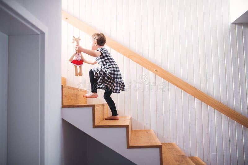 Een klein kind met een zacht stuk speelgoed die omhoog de treden lopen royalty-vrije stock afbeeldingen