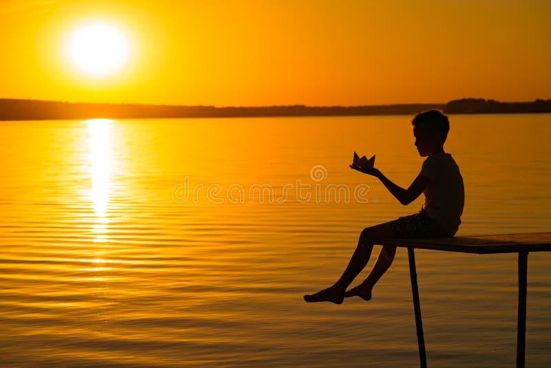 Een klein kind is op een brug met origami in de vorm van een boot in zijn handen bij zonsondergang De benen van het verminderde k stock foto's