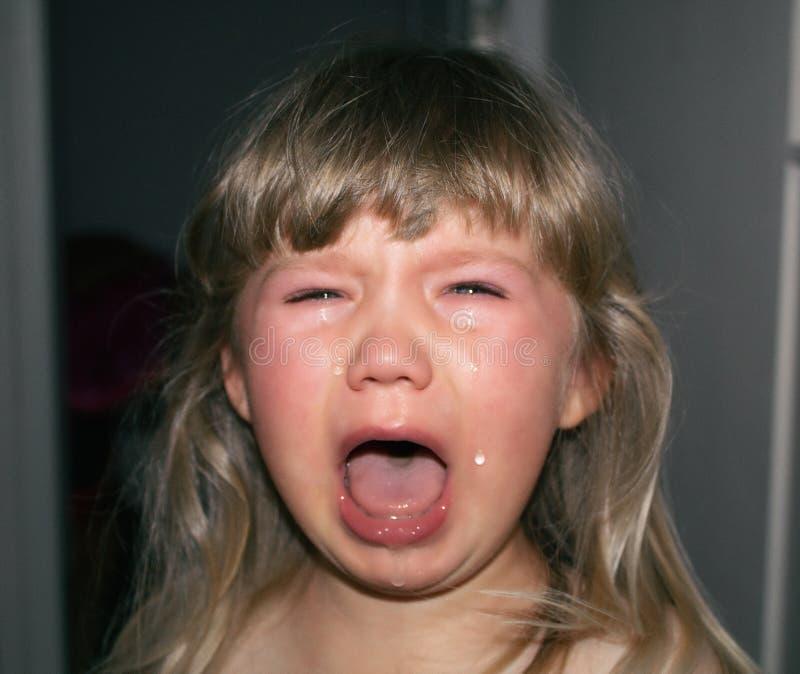 Een klein kind schreeuwt met scheuren en het kwijlen Kinderen` s hysterie stock afbeelding