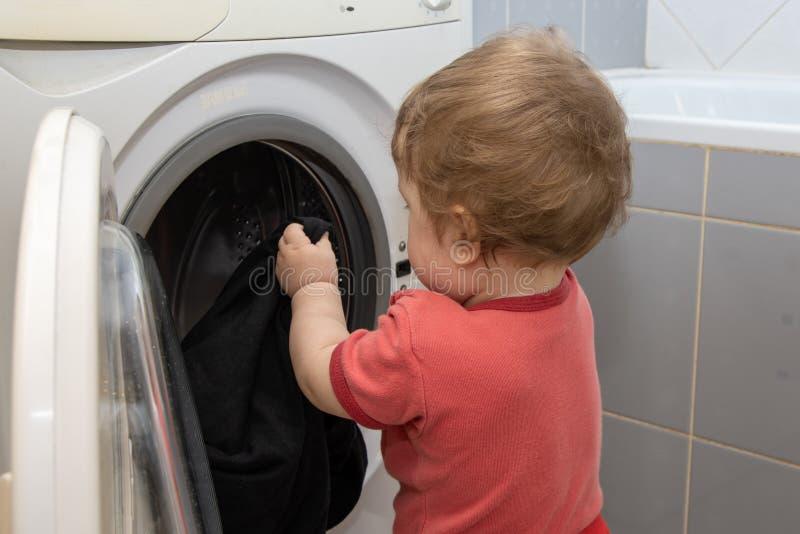 Een klein kind trekt dingen uit de wasmachine, een jonge medewerker stock afbeeldingen