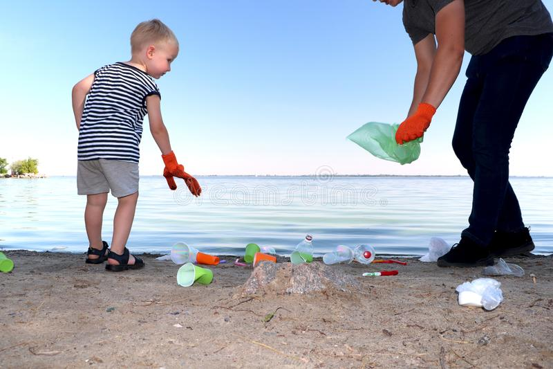 Een klein kind verzamelt afval op het strand Zijn papa richt zijn vinger waar te om huisvuil te werpen De ouders onderwijzen kind royalty-vrije stock fotografie