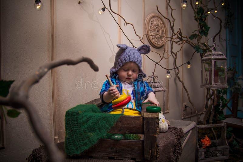 Een klein kind zit in een houten doos in een geheimzinnig bos royalty-vrije stock fotografie
