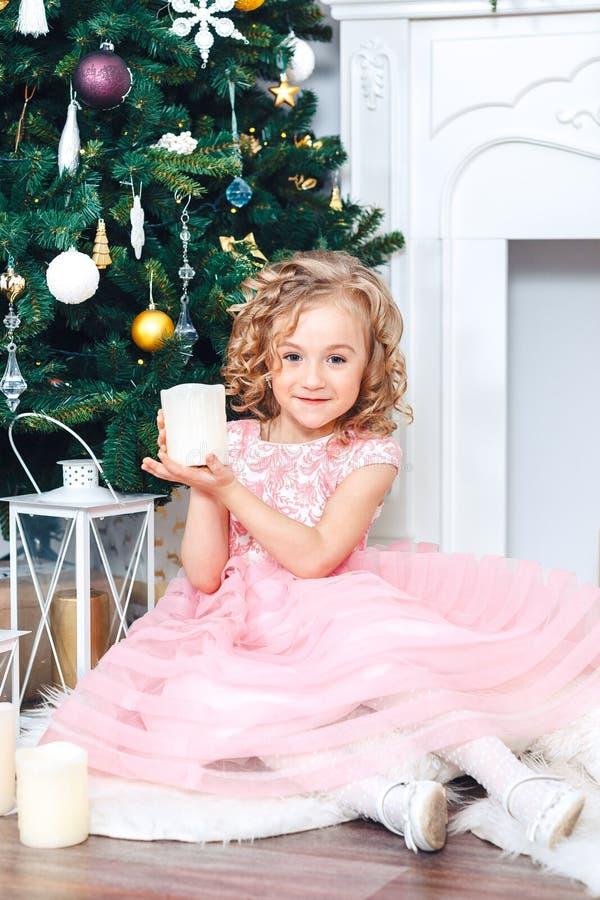 Een klein kind zit onder een Kerstboom in een mooie roze kleding, houdt een kaars, rond giften stock foto's