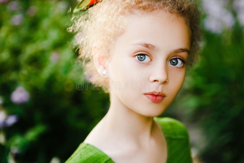 Een klein, krullend meisje in een groene kleding royalty-vrije stock afbeeldingen