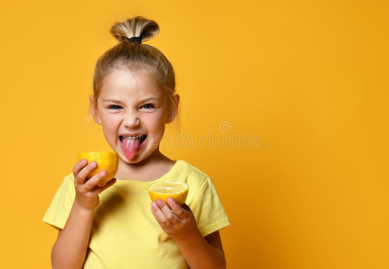 Een klein lachend schattig meisje in een geel T-shirt met halven verse, rijpe citroenvruchten en tongtongen op gele achtergrond stock afbeeldingen