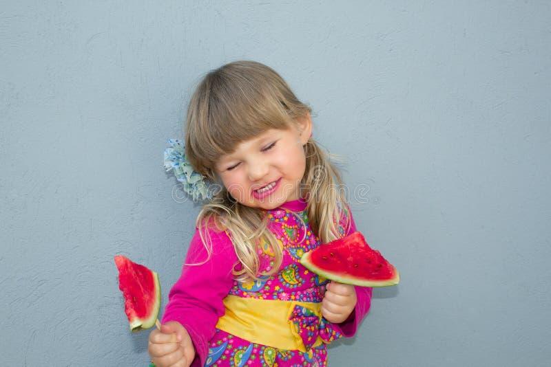 Een klein meisje bevindt zich door de muur en houdt twee watermeloenen op een stok Een vrolijke glimlach royalty-vrije stock foto
