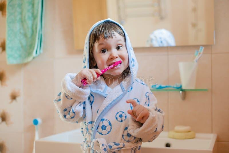 Een klein meisje borstelt haar tanden Een kind in een badjas in de badkamerswassen royalty-vrije stock afbeelding