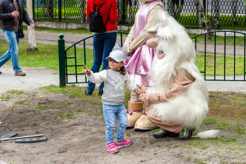 Een klein meisje communiceert met een pop van grote gestalte Buba de Brownie stock foto's