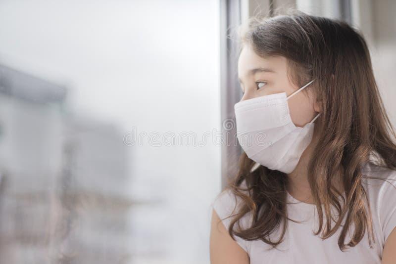 Een klein meisje dat een masker draagt om Covid-19 te beschermen staat dicht bij het raam en is triest Het meisje werd ziek en ka royalty-vrije stock fotografie