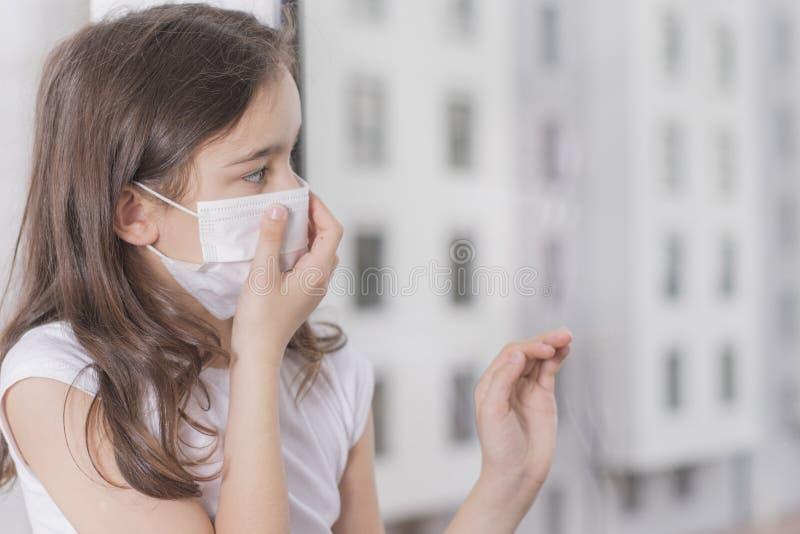 Een klein meisje dat een masker draagt om Covid-19 te beschermen staat dicht bij het raam en is triest Het meisje werd ziek en ka royalty-vrije stock foto