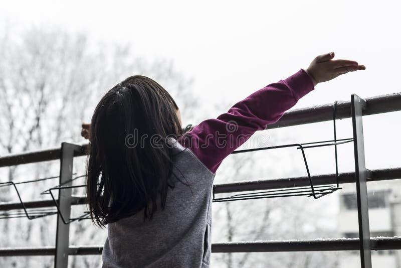 Een klein meisje dat van de eerste sneeuw geniet royalty-vrije stock foto's