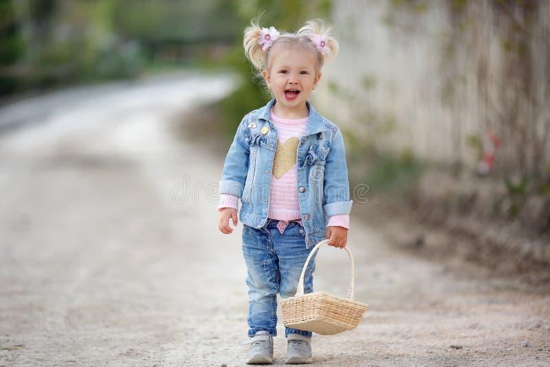 Een klein meisje in de gangen van een denimkostuum alleen in een de lentepark met een rieten mand in haar handen royalty-vrije stock foto's