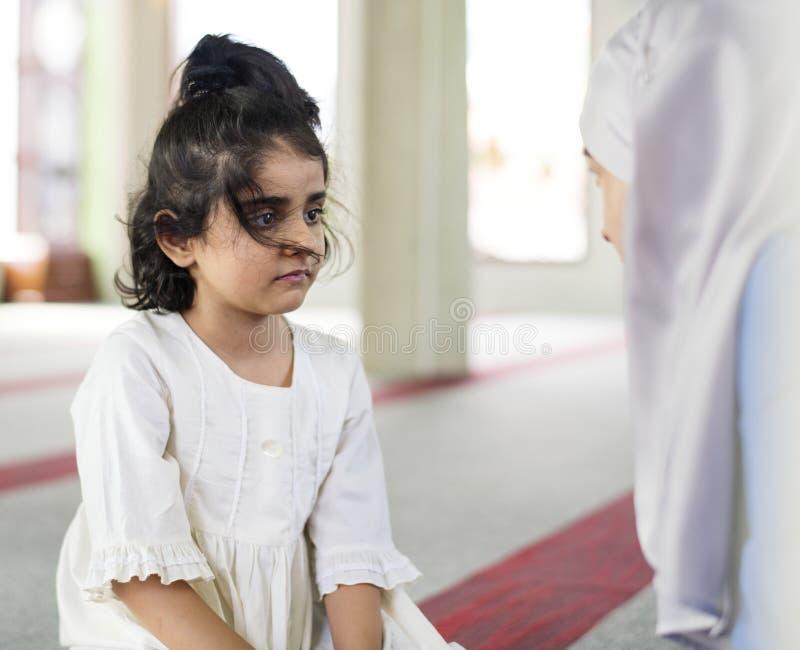 Een klein meisje in de moskee met haar moeder tijdens Ramadan stock afbeelding