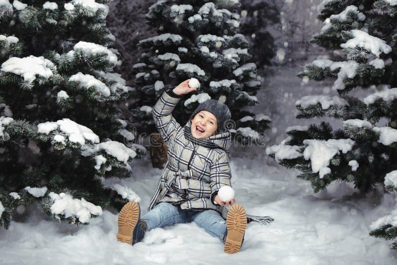 Een klein meisje in de winter kleedt het spelen met sneeuw op een sneeuwdieweide door sparren wordt omringd Kerstmistak en klokke stock fotografie