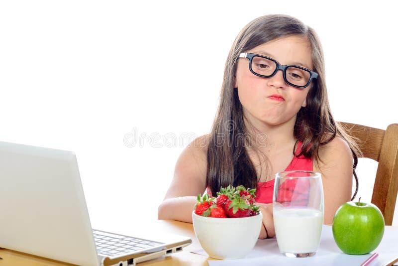 Een klein meisje die bij haar bureau zijn snack bekijken stock foto