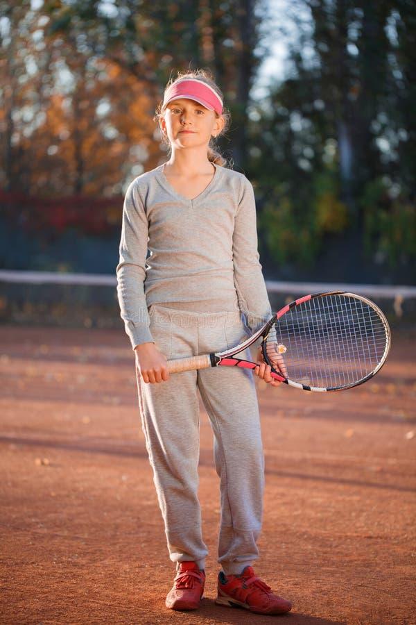 Een klein meisje, die terwijl status, die handen met een tennisracket houden stellen Het concept sport royalty-vrije stock afbeelding