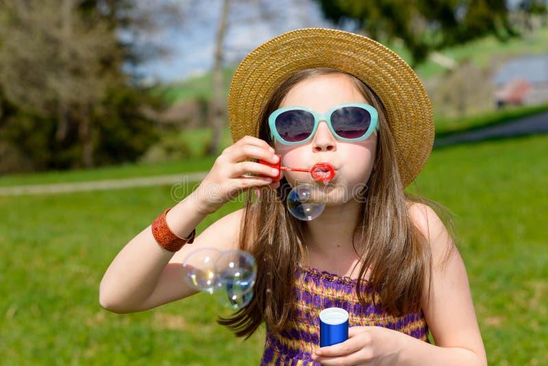 Een klein meisje die zeepbels maken stock foto's