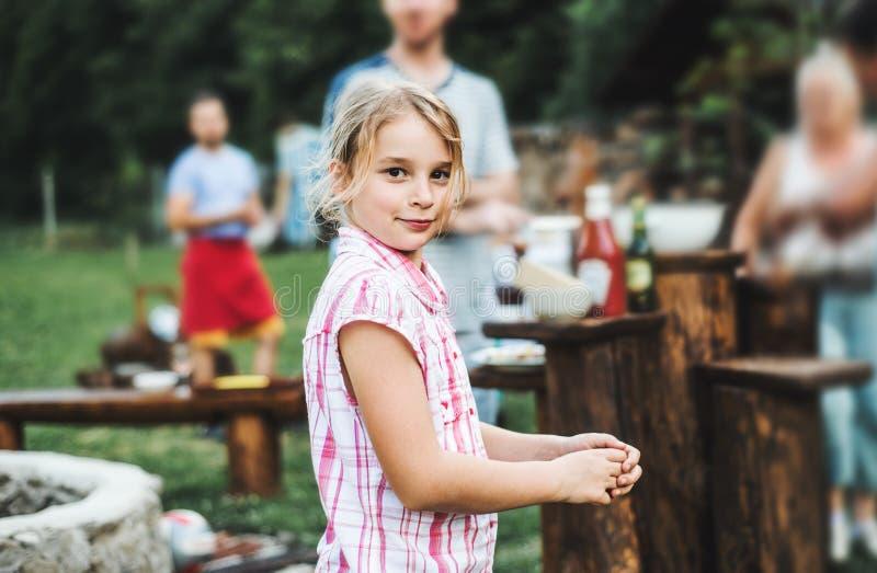 Een klein meisje die zich in openlucht op een partij van de barbecuegrill in de binnenplaats bevinden stock foto's