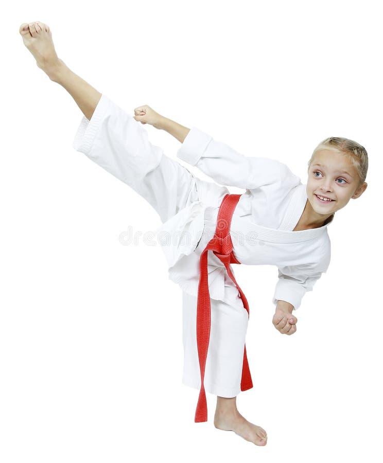 Een klein meisje in een witte kimonoklappen roundhouse schopt geïsoleerde achtergrond royalty-vrije stock afbeeldingen