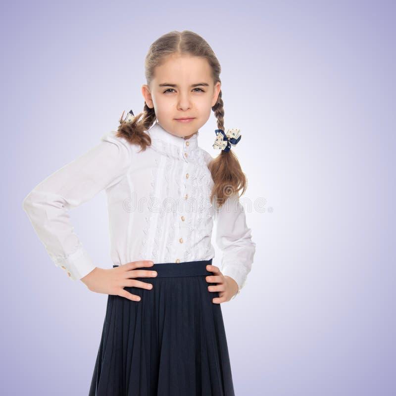 Een klein meisje in een witte kleding en een donkere rok stock afbeelding