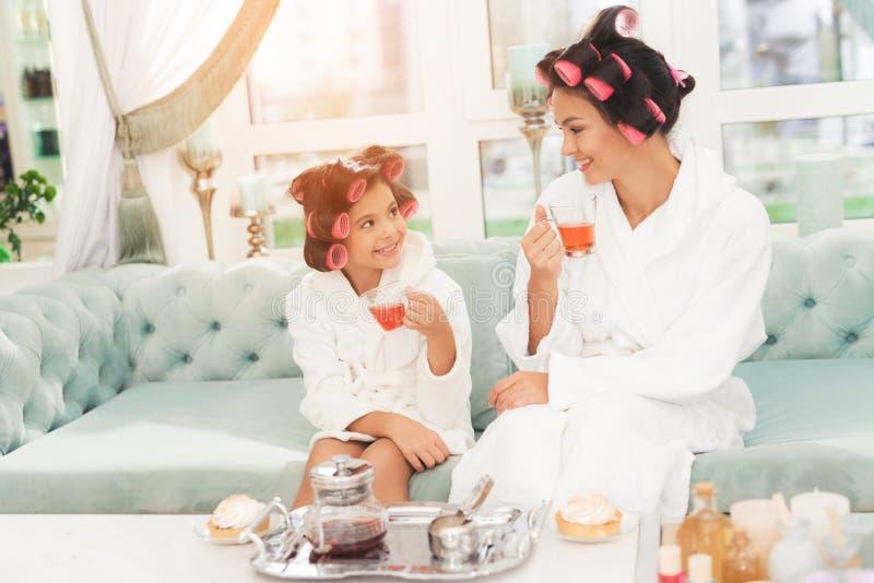 Een klein meisje en haar moeder zitten op laag Zij hebben krulspelden op hun hoofden royalty-vrije stock fotografie