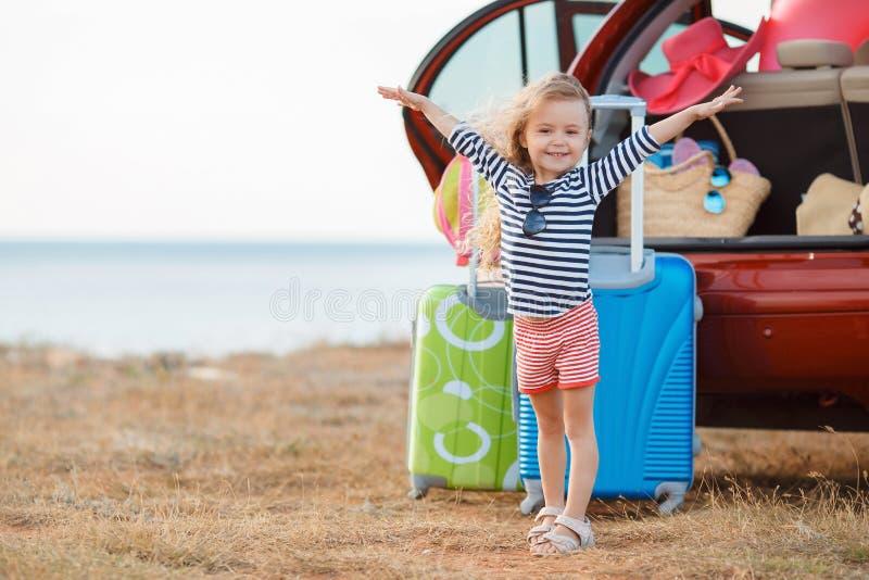 Een klein meisje gaat op een reis op een rode auto stock fotografie