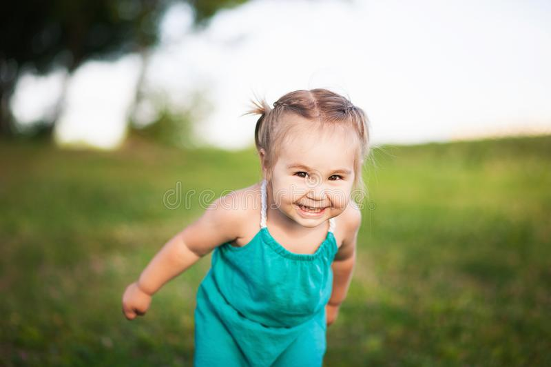 Een klein meisje in groene sarafan glimlachen in de zomer tegen een achtergrond van groen jong gras royalty-vrije stock afbeelding