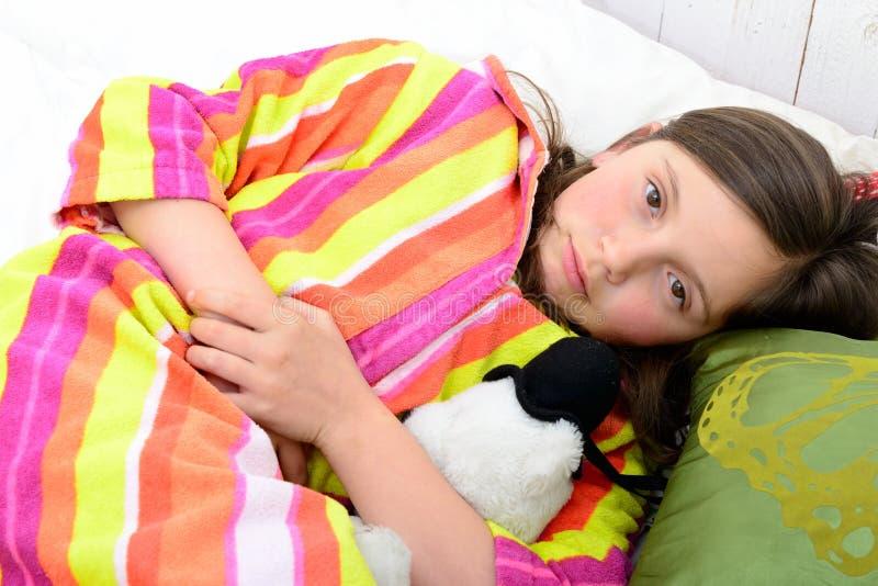Een klein meisje in haar bed heeft een maagpijn stock foto's