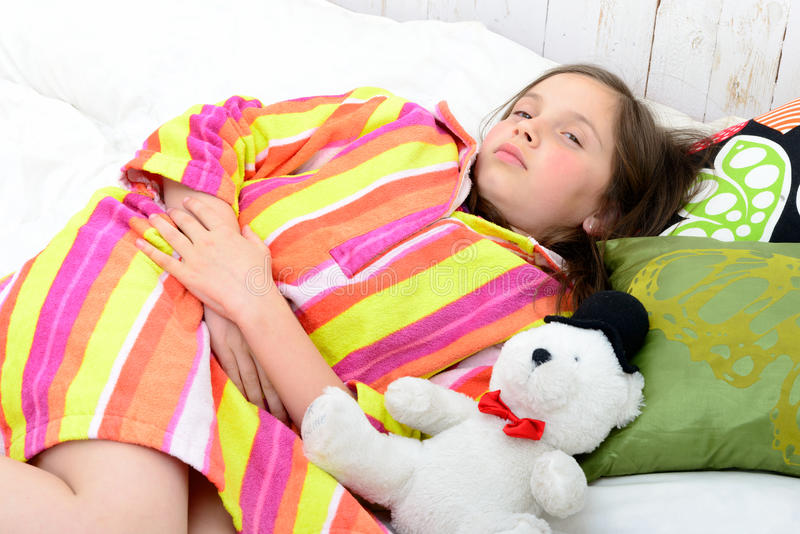 Een klein meisje in haar bed heeft een maagpijn royalty-vrije stock foto's