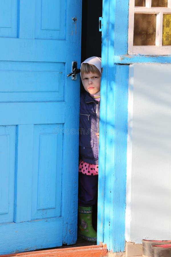 03 05 2015 Een klein meisje in een headscarf bekijkt haar door de open deur royalty-vrije stock foto's