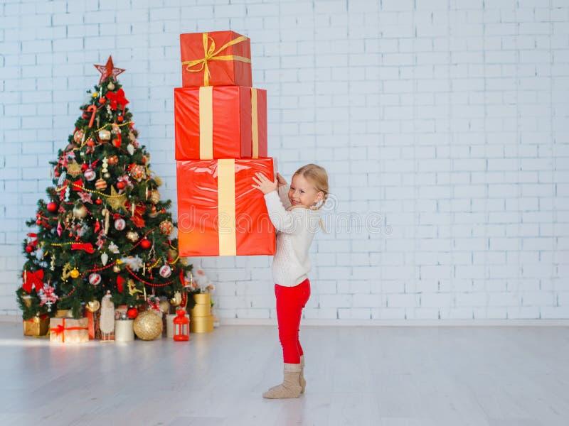 Een klein meisje heeft heel wat giften op een witte bakstenen muurachtergrond royalty-vrije stock afbeeldingen