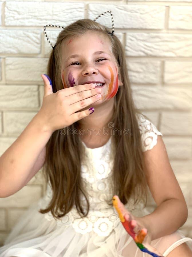 Een klein meisje heeft pret, gekleurde verf op haar handen stock afbeeldingen