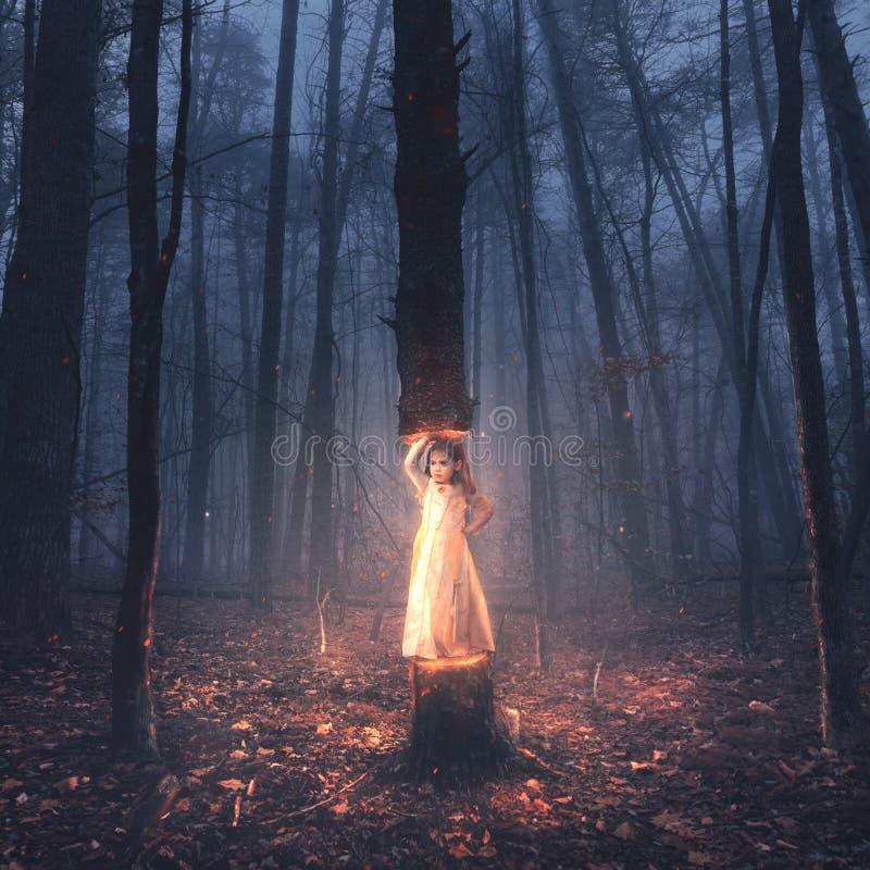 Een klein meisje heft een boom op stock fotografie