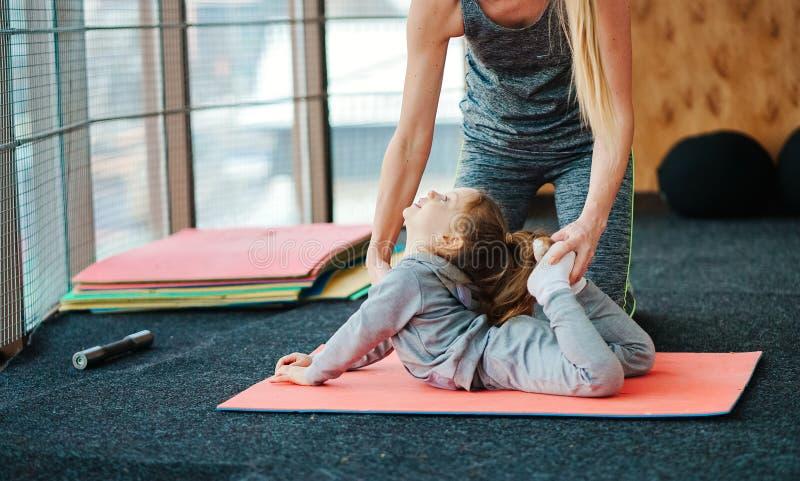 Een klein meisje herhaalt oefeningen voor haar moeder stock fotografie