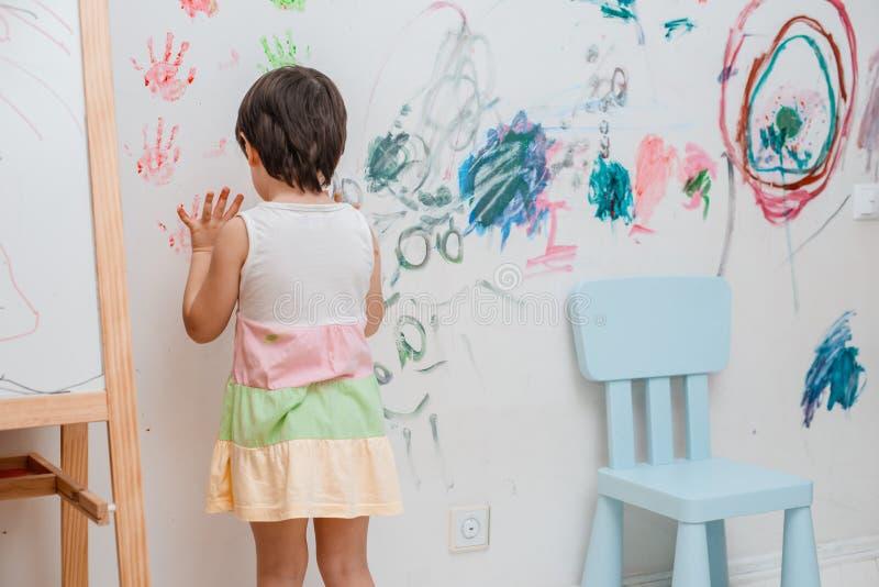 Een klein meisje, 3 jaar oud, schilderde een overspannen blik met verf en een borstel op de muur van haar ruimte royalty-vrije stock afbeeldingen