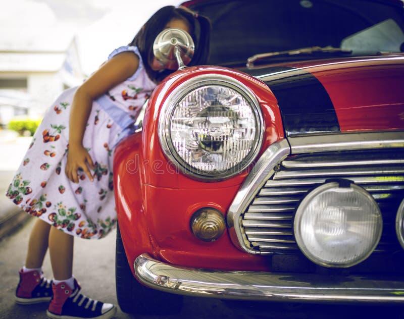 Een klein meisje kijkt haar gezicht met spiegel van uitstekende auto, Headli stock afbeeldingen