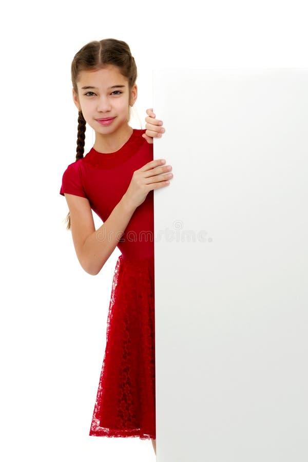 Een klein meisje kijkt van achter een lege banner stock foto