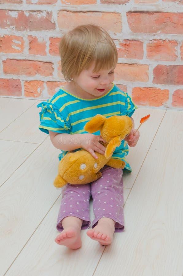 Een klein meisje, een kind met een Lolly en een stuk speelgoed hert stock afbeelding